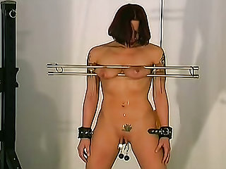 Watch this redhead tied up with a rope getting a tits torture by her master while hanging in this BDSM video.